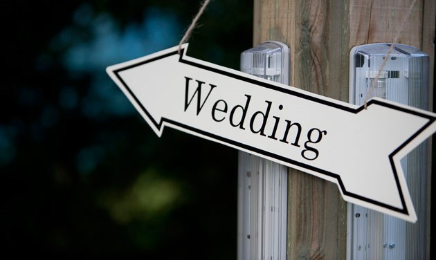 white direction arrow pointing to the left with the word wedding