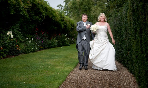 bride and groom walking on gravel path next to tall hedge at blake hall