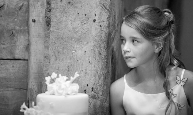 child bridesmaid leaning against wooden post in a barn next to a wedding cake