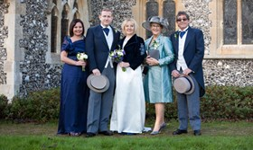 traditional wedding group photo of five people in church grounds
