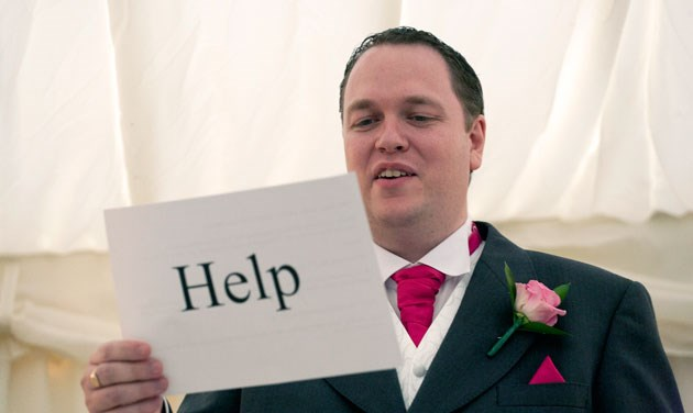 groom holding words to his speech with the word help written on the back
