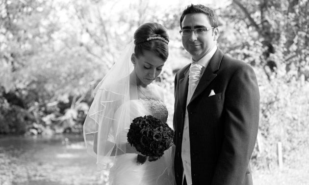 black and white photo of bride and groom standing by fountain at Channels Estate Essex