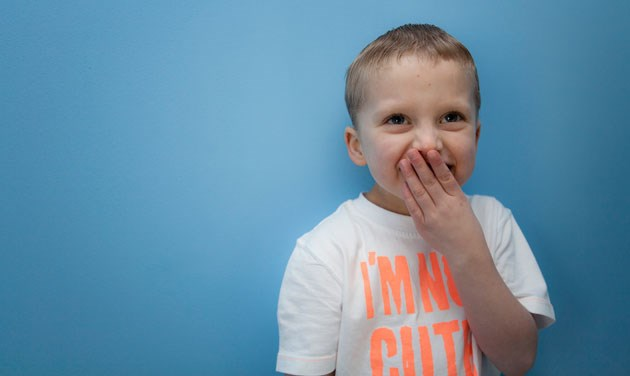 young boy with his hand to mouth against a blue background