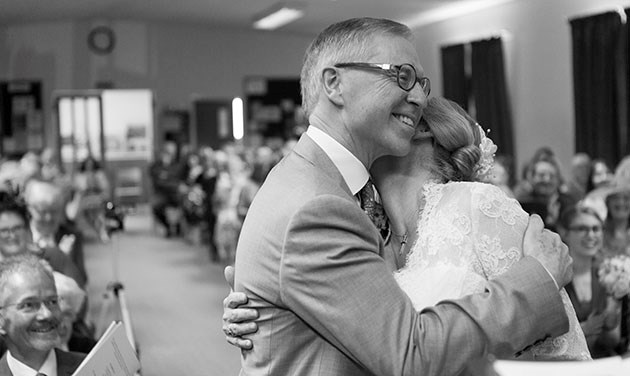 reportage photo of bride hugging groom seconds after being named man and wife