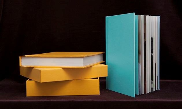 pile of yellow wedding albums next to a standing turquoise colour wedding album