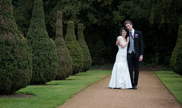 bride and groom in middle of avenue of bushes at Hylands House
