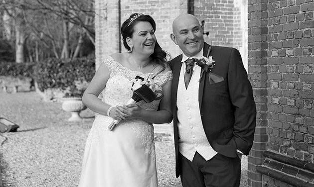 candid image of bride and groom at foot of tower at Leez Priory Chelmsford