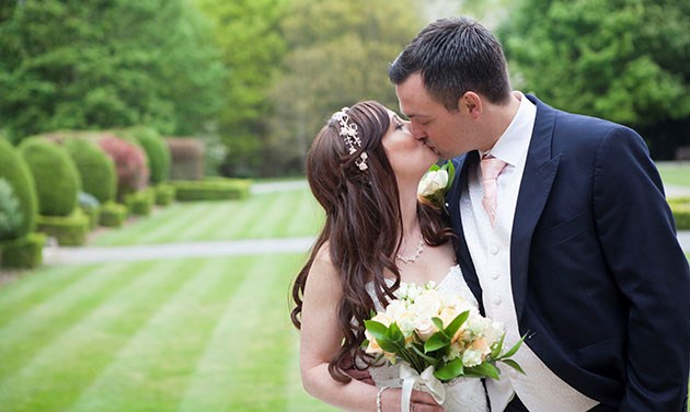 bride kissing groom with grounds of Theobalds Estate in background