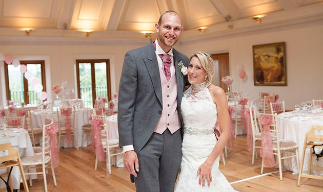 Newlyweds at Stock Brook wedding venue with decorated room in the background