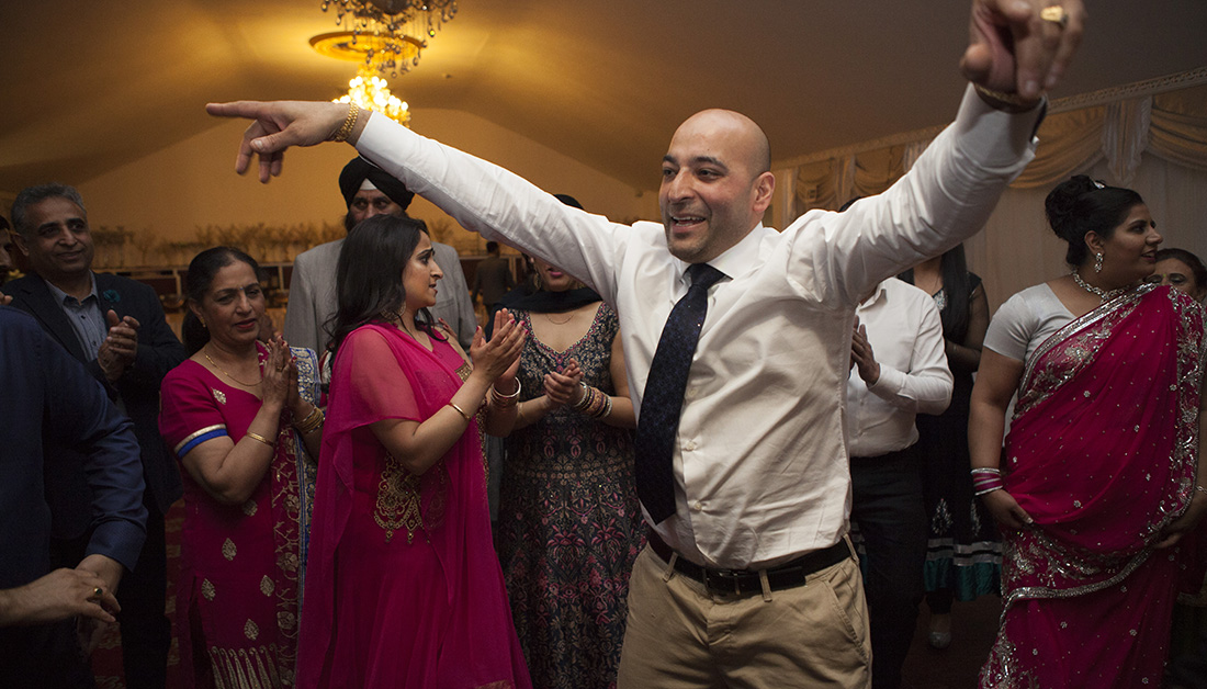 man in middle of dance floor with arms outstretched at an Indian party