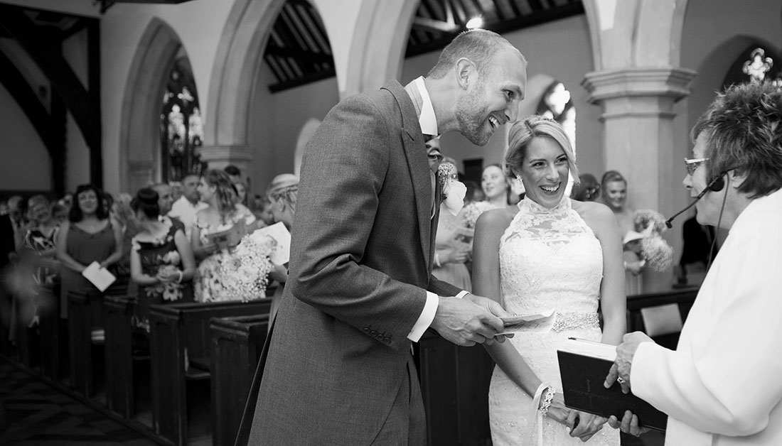 bride and groom laughing with vicar during wedding ceremony in an Essex church