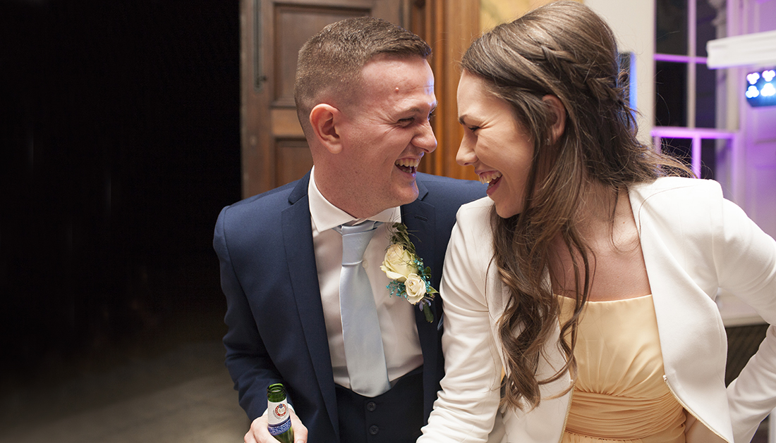 two people looking at each other and laughing during the wedding party at Hylands House Essex