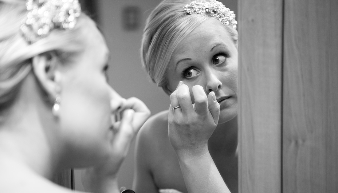 bride looking in mirror and putting on eye make up