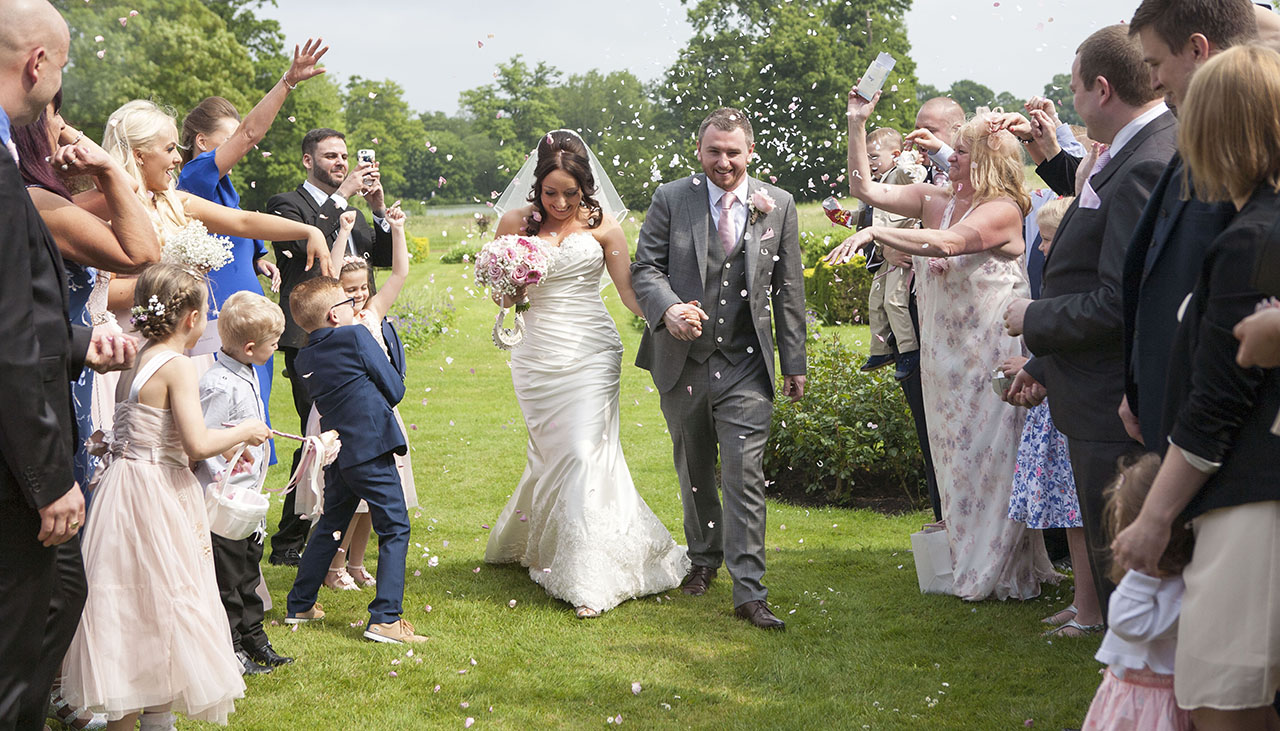bride and groom walking between two rows of people as they throw confetti