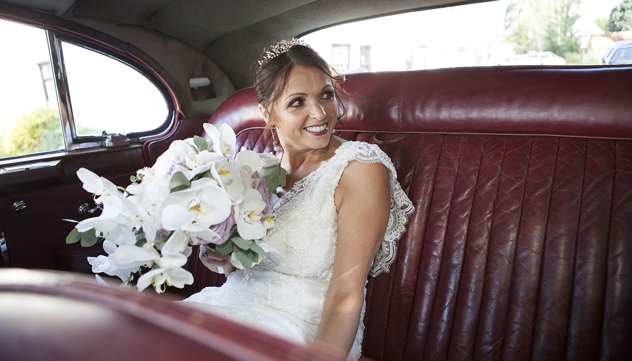 bride with bouquet of flowers on red leather back seat of car looking to the right