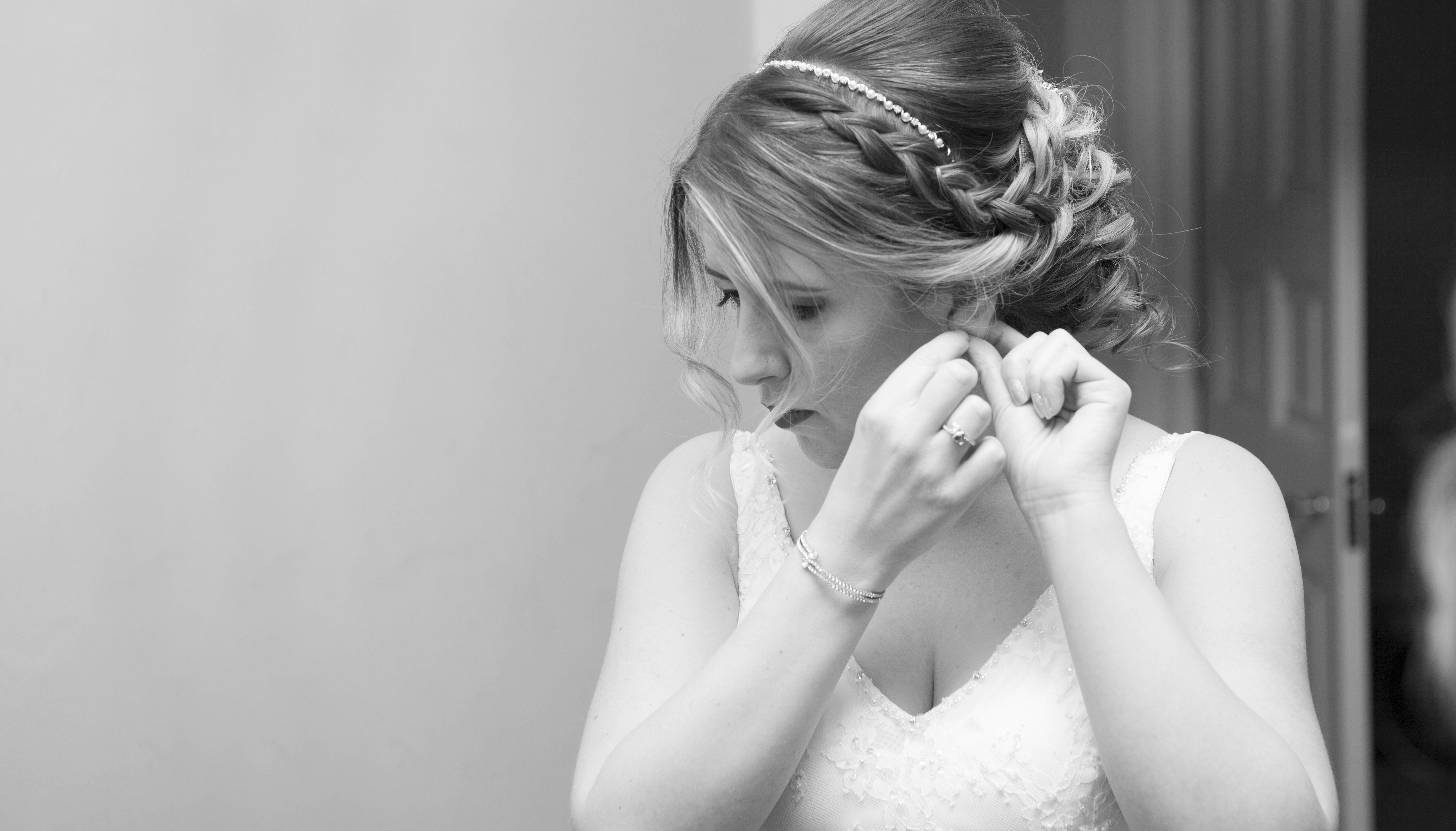 black and white photo of bride putting on earring during bridal preparations at Hylands House Essex