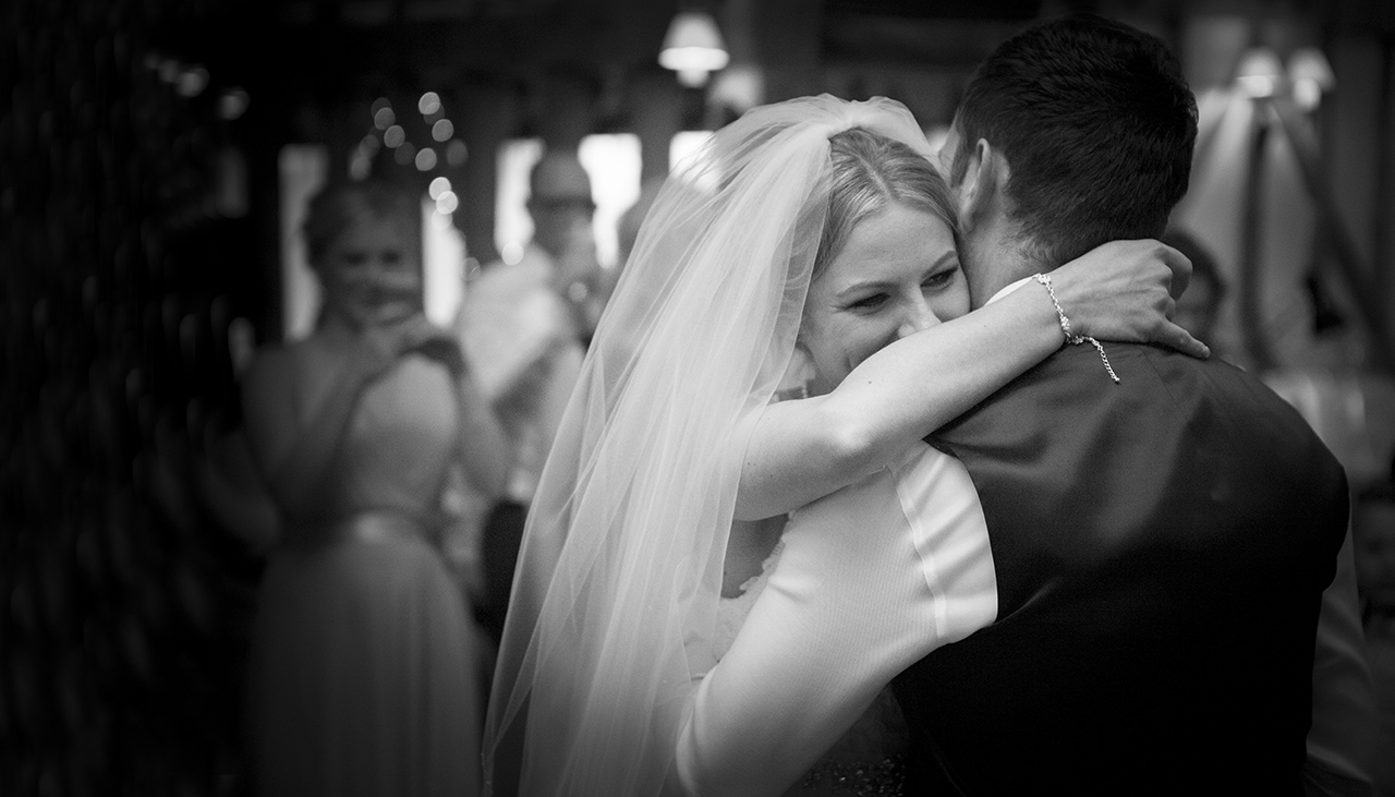 bride with veil laughing with her arms around the groom's neck during a wedding first dance