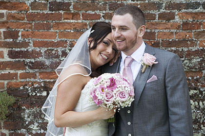bride holding pink flowers with her head on the groom against an old brick wall background