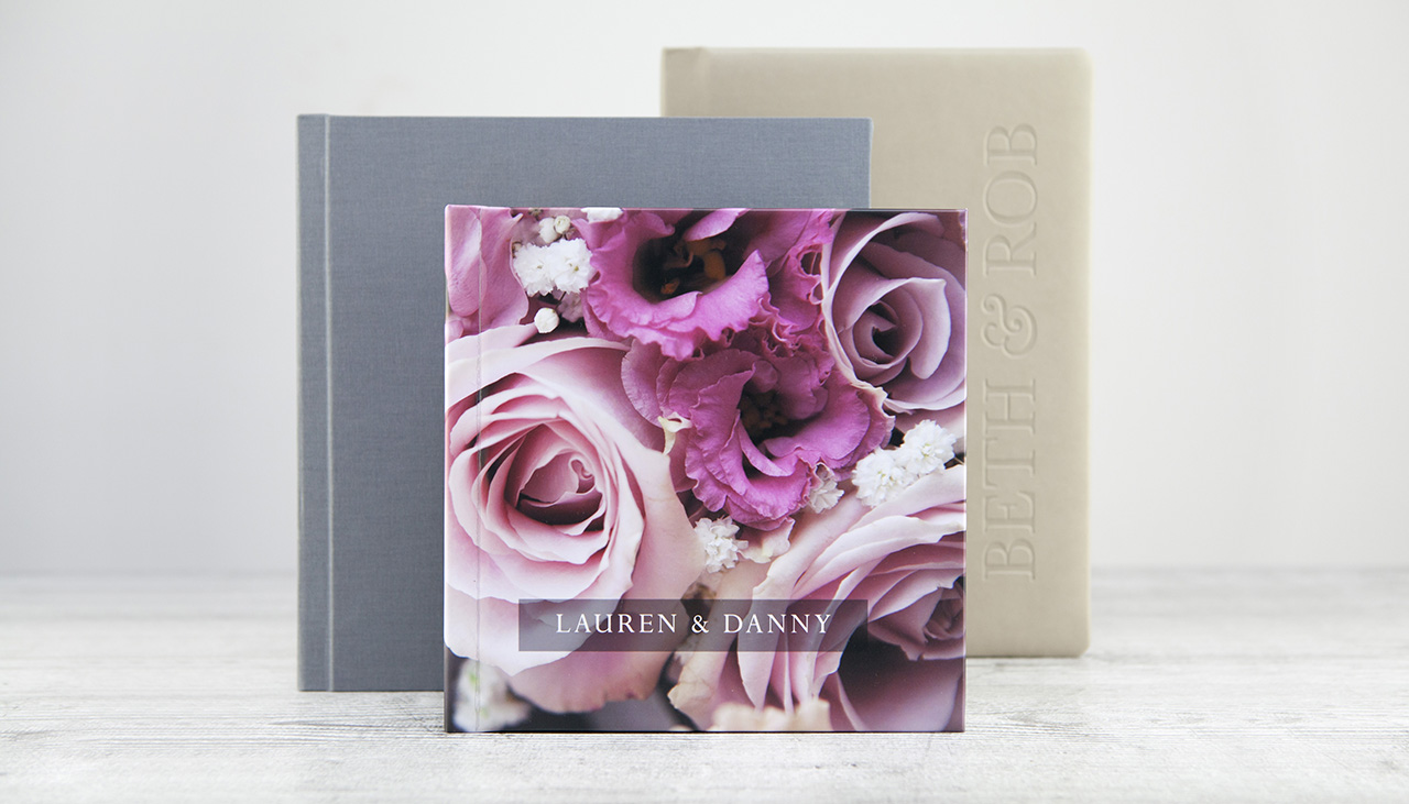 three different sized weddings albums standing upright showing three different cover designs