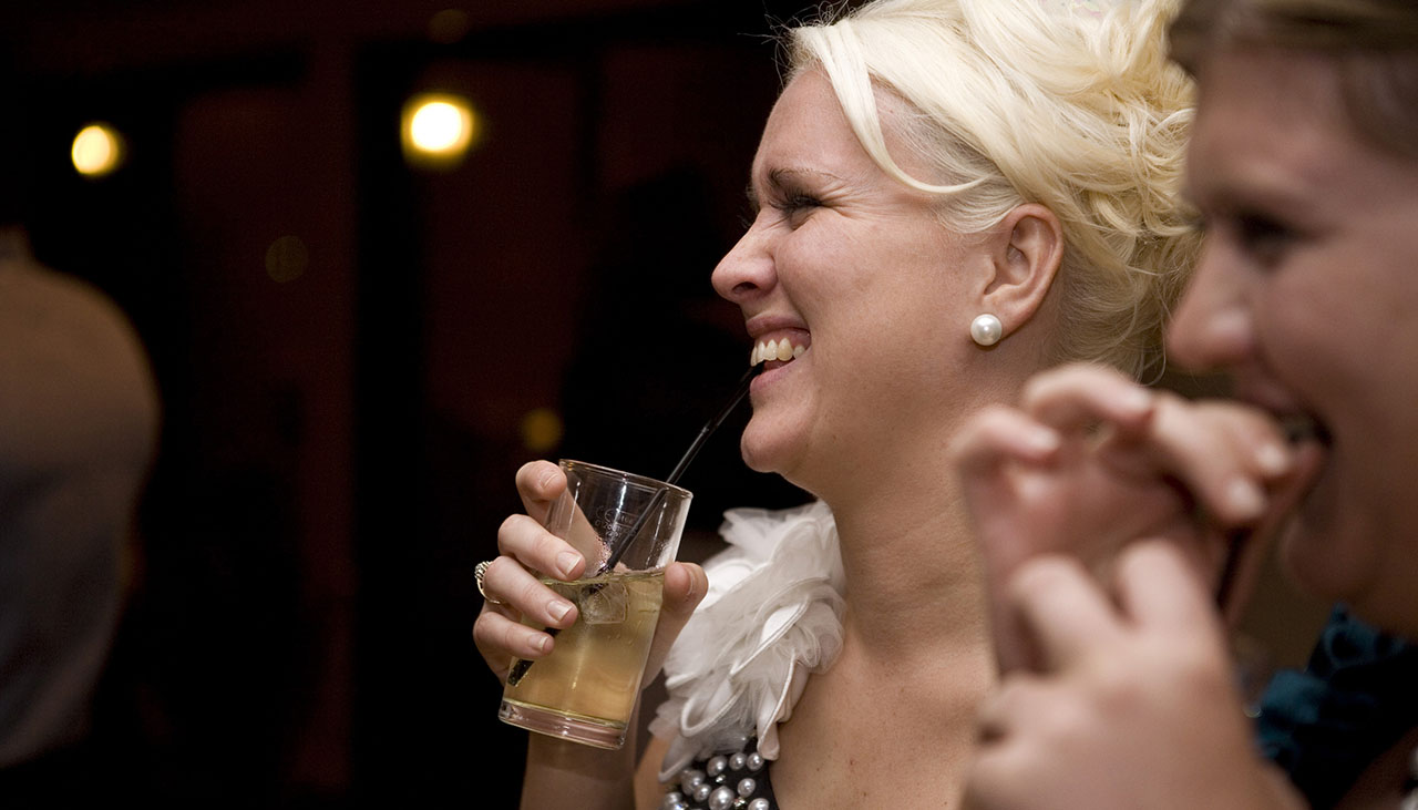 girl holding a drink and laughing at a party against black background