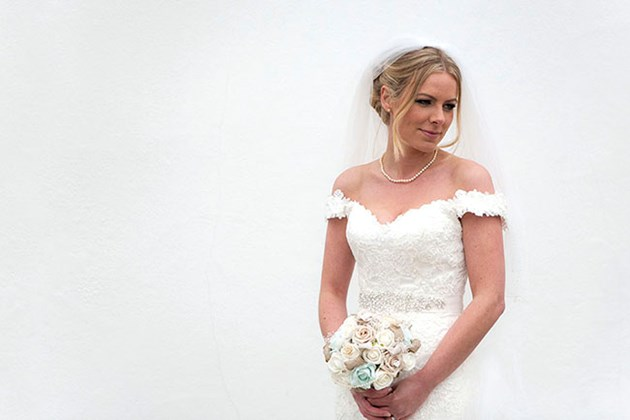 contemporary portrait of bride looking down to right against a white wall