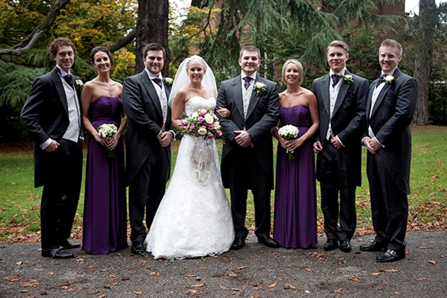 traditional wedding group photo of bride and groom with ushers and bridesmaids in church grounds