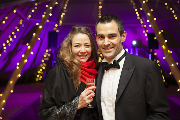 Two guests at black tie party looking at camera with sparkling lights in the background
