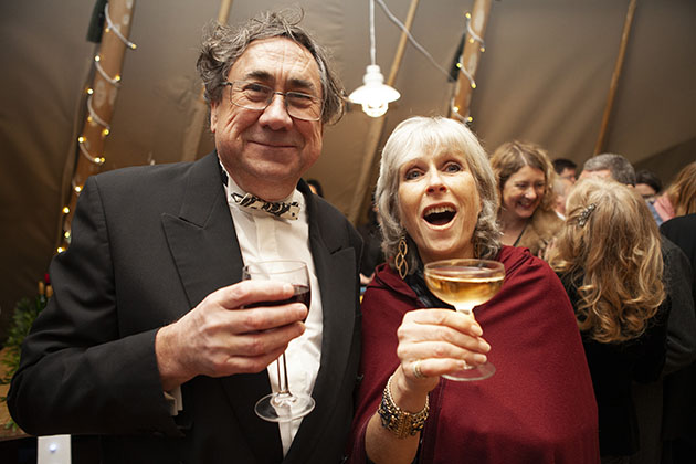 Two party guests with drinks in hand