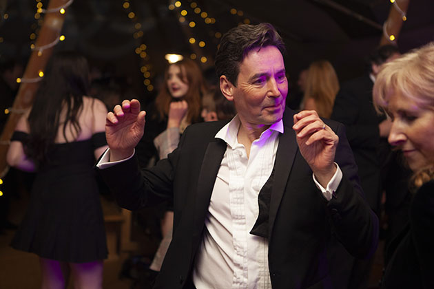 Man in suit dancing at a party