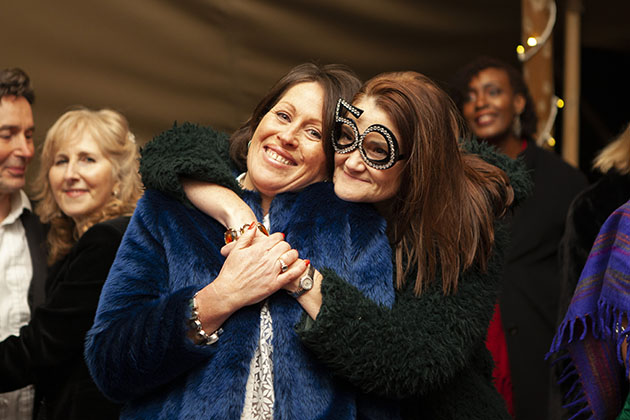 Two women hugging at a social function
