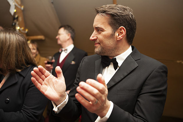 Man in black tie looking to the side and clapping