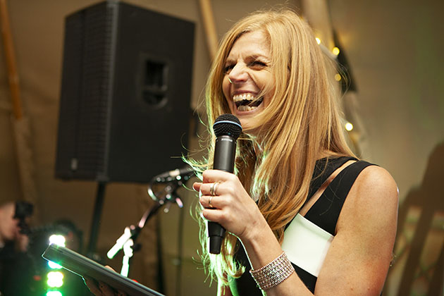 Woman on stage with a microphone and laughing