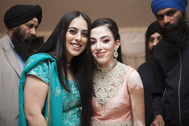 Two young Sikh girls in traditional dress looking at the camera