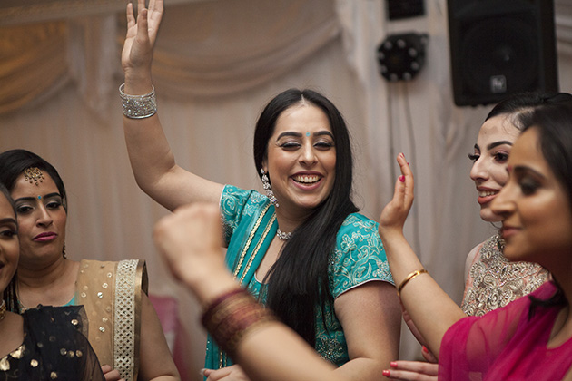 Women dancing with hands in the air at an Indian birthday party