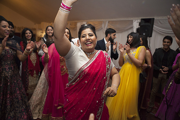 Woman in red sari dress on the dance floor with arms in the air