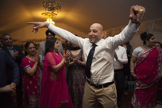 man on dance floor with arms outstretched an Indian party