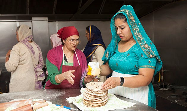 Indian women in a kitchen making chapati