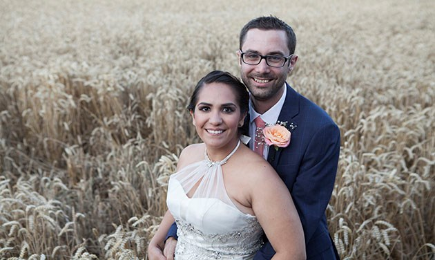 Bride and groom standing together at Vaulty Manor with a wheat field in the background