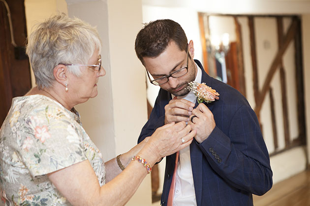 Groom having help fixing his buttonhole