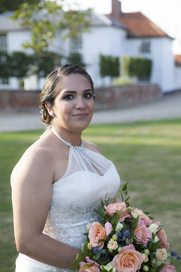 Portrait of bride holding a bouquet with Vaulty Manor in background