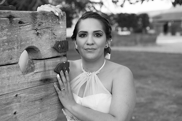 Relaxed portrait of bride holding wooden stocks