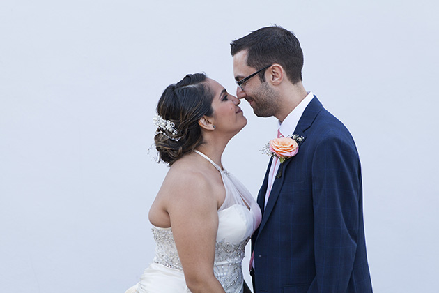 Bride and groom facing each other with their noses together standing by a white wall