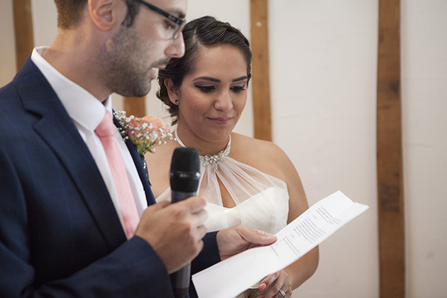 Groom reading a speech as his wife looks on