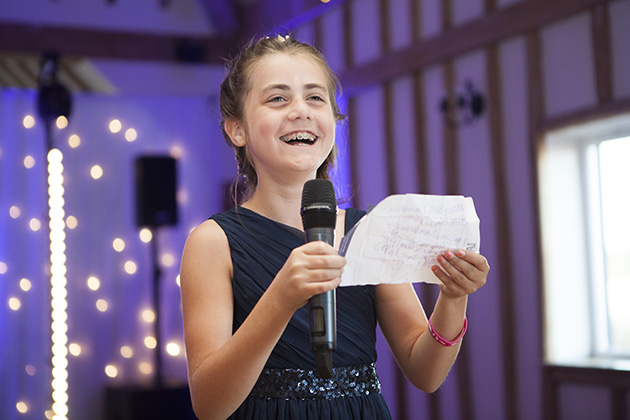 Young bridesmaid making a wedding speech with purple coloured lighting in the background