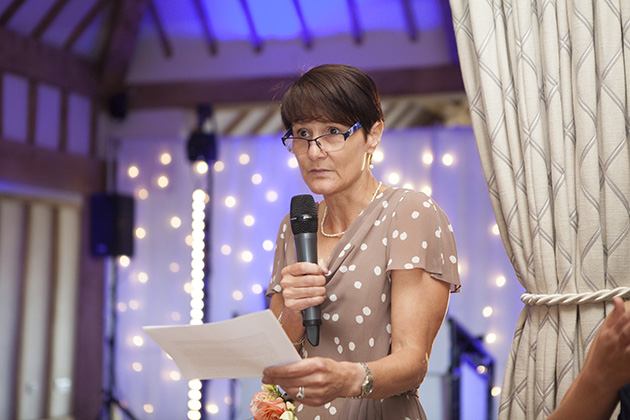 Woman making a wedding speech with purple coloured lights in background