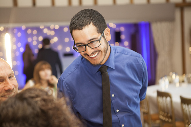 Wedding guest wearing a blue shirt talking to other guests