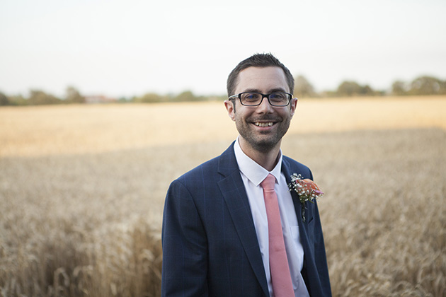 Relaxed portrait of groom with field of wheat in background