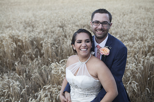 Fun portrait of bride and groom with a field of wheat in the background