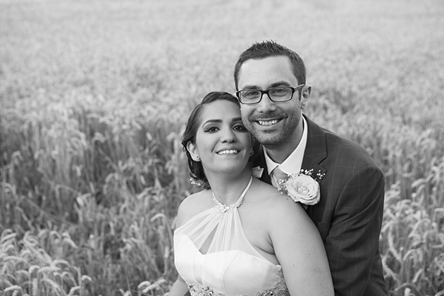 Black and white portrait of bride and groom with a field of wheat in the background