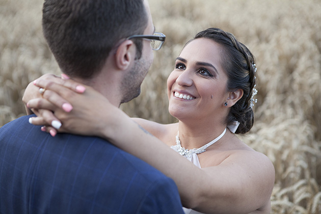 Close up of bride with her hands around the neck of the groom with a field of wheat in the background